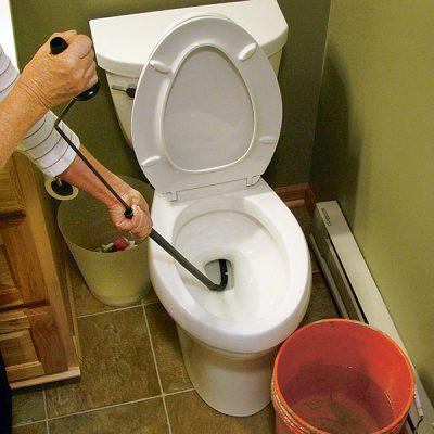 déboucheur qui débouche une toilette avec un furet manuel