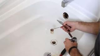 plombier qui débouche une baignoire