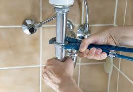 plombier qui répare un lavabo
