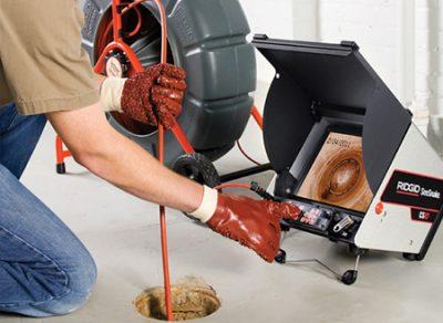 plombier qui inspecte la canalisation
