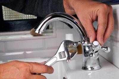 plombier qui installe un robinet