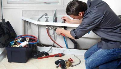 Plombier qui effectue un raccordement d'eau à la baignoire