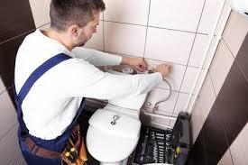 Plombier qui répare une toilette qui fuit