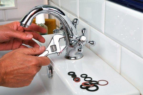 plombier qui répare un robinet