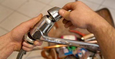 plombier qui remplace un robinet