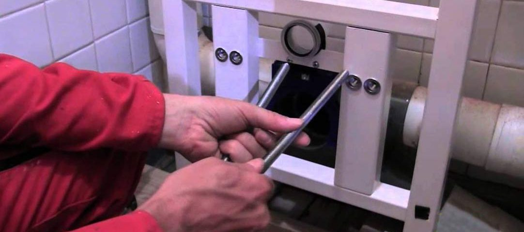 plombier qui installe une toilette suspendue