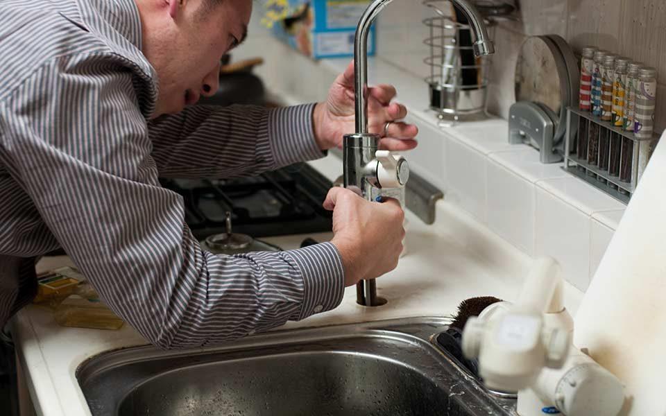 plombier qui débouche un robinet