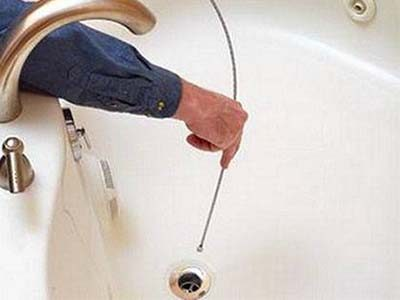 Le déboucheur débouche la baignoire avec un câble de tarière
