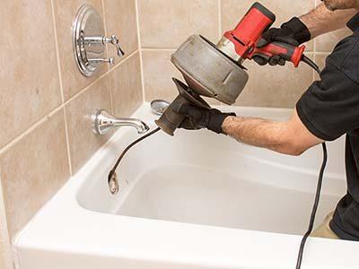 Le déboucheur déboucle la baignoire ar le trop plen avec un furet de plomberie