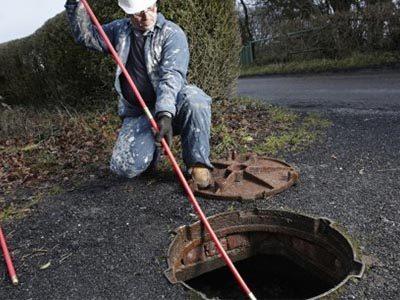 Vérification du niveau de boue dans la fosse septique